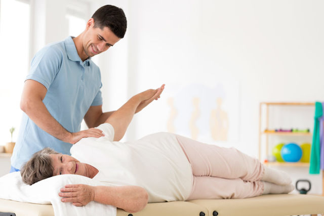 Physical therapist stretching arm of older woman for frozen shoulder blog