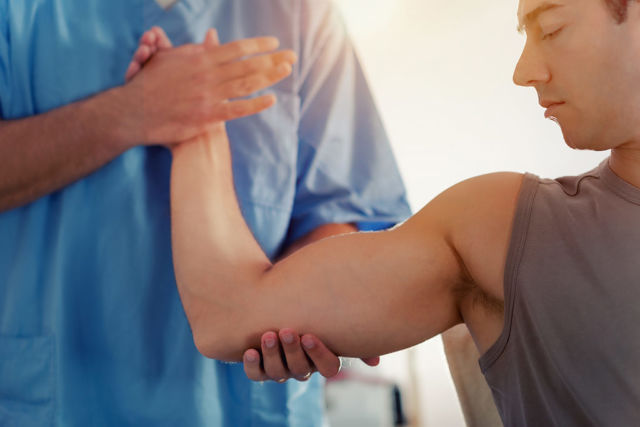 Doctor checking man's arm for arthroscopy blog