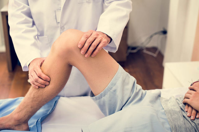 Doctor examining knee for knee replacement surgery blog