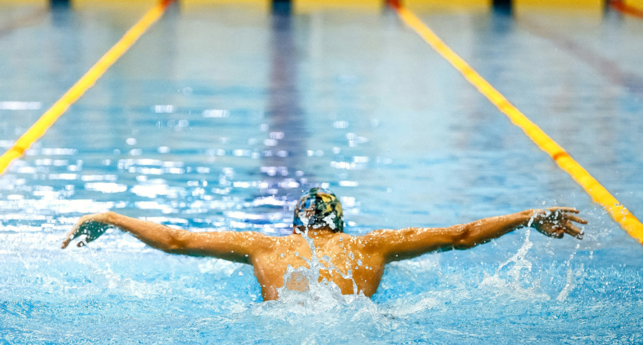 Single swimmer athlete swimming butterfly stroke to depict strong, healthy shoulders
