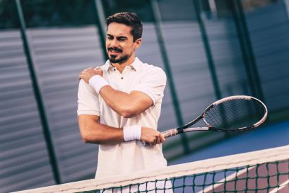 Handsome man on tennis court. Young tennis player. Shoulder pain